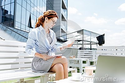 Good-looking fashionable remote worker working on summer terrace