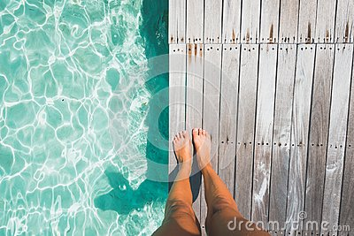 Tanned feet of a woman standing on a wooden deck by tropical ocean