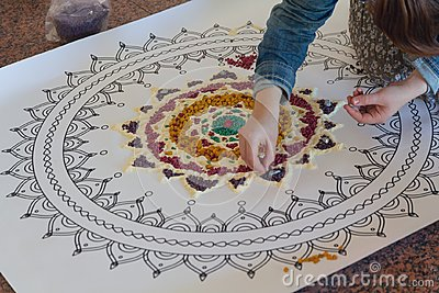 Hand of the woman creating a mandala