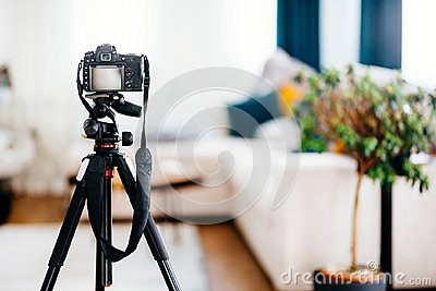 Camera on tripod taking photographs of interior design, furniture and houses