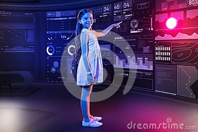 Happy schoolgirl having a productive day and pointing to the futuristic device