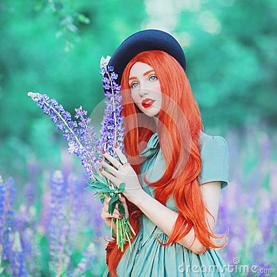 Valentines Day background. Young fairy redhead girl with very long hair on lupine background. Valentines Day beauty woman in mint