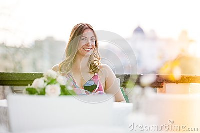 Beautiful and charming smiling woman sitting outdoor