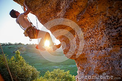 Picture of man clambering over rock.
