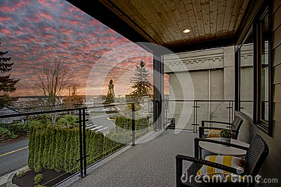 Modern house exterior with a deck at sunset.