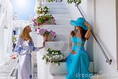 Two attractive traveler woman are enjoying the white, picturesque alleys of Mykonos
