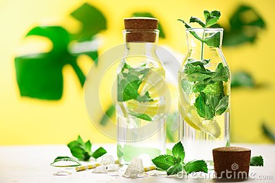Citrus lemonade - mint, lemon and tropical monstera leaves on yellow background. Detox drink. Summer fruit infused water