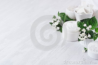 Soft pure white delicate cosmetics set of cream, salt, clay decorated white flowers, green leaves on light soft wooden background.