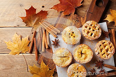 stock image of delicious mini apple pies on rustic wooden table. autumn pastry desserts.