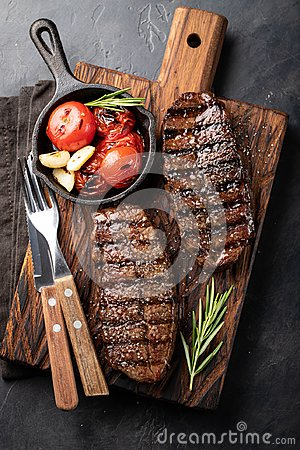 Closeup ready to eat steak Top Blade beef breeds of black Angus with grill tomato, garlic and on a wooden Board. The finished dish