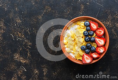 Breakfast corn flakes with milk and fresh berries, strawberries, blueberries on a dark background. Top view, copy space. Dietary f