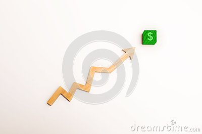 Wooden arrow up arrow points to a green block with a dollar symbol. The concept of revenue growth and cost, increase in profits. I