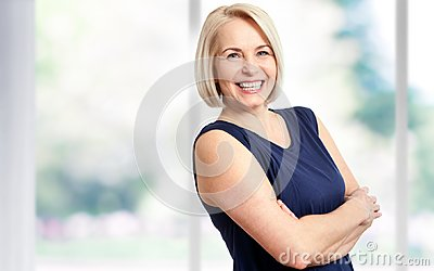 Attractive middle aged woman with a beautiful smile near the window.