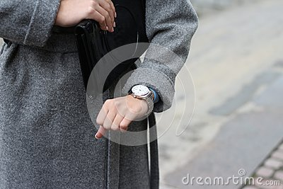 a young girl in a gray coat looks at her wristwatch, checks the time, looks at her watch. hurry to a meeting, be late. punctuality