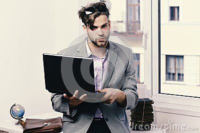 Working online and gadgets concept. Cool guy sits on table and works. Man or manager with bristle and serious face in
