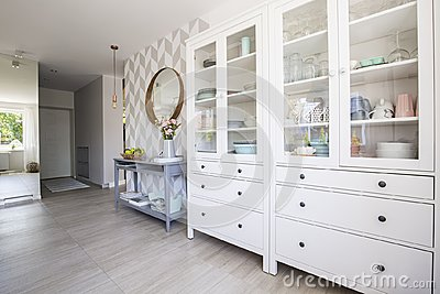 White kitchen cupboard with pastel dishes and blue console table