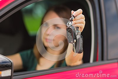 Beautiful girl with keys from car in hand, concept of buying a new car, feelings of joy from shopping