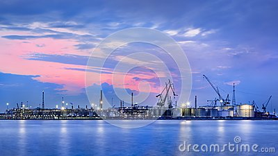 Panorama of a petrochemical production plant against a dramatic colored sky at twilight, Port of Antwerp, Belgium.