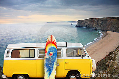 Van and surf board at a beach