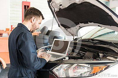 Worker Using Laptop To Detect Malfunction In Car At Garage