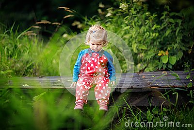 Cute adorable toddler girl sitting on wooden bridge and throwing small stones into a creek. Funny baby having fun with