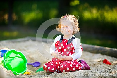 Cute toddler girl playing in sand on outdoor playground. Beautiful baby in red gum trousers having fun on sunny warm
