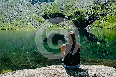 A girl sitting on a rock, looking at a spectacular view of the mountain reflecting in the lake.