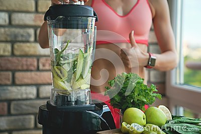Close up of young woman with blender and green vegetables making detox shake or smoothie at home