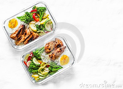 Rice, stewed vegetables, egg, teriyaki chicken - healthy balanced lunch box on a light background, top view. Home food for office