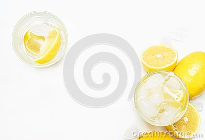 Summer refreshing drink, cold water with ice and lemon, white ba