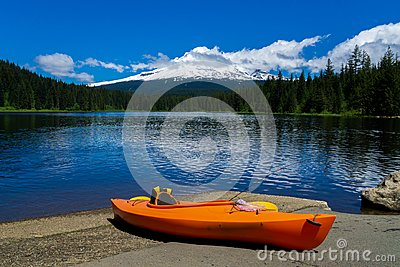 Kayak lying on the ground at Trillium Lake with the Mt. Hood in the background on a sunny day of early summer. Recreation and fish