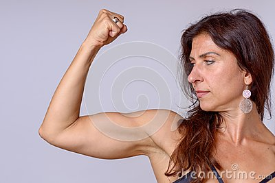 Strong fit mature woman flexing her arm muscles