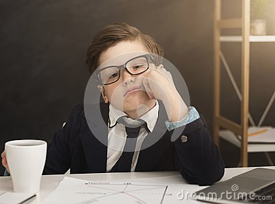 stock image of small business boy got bored in office