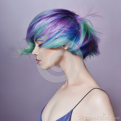 Portrait of a woman with bright colored flying hair, all shades of purple. Hair coloring, beautiful lips and makeup. Hair