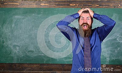 Man bearded teacher or educator hold head chalkboard background. Pay attention to your behaviour and manners. Teacher