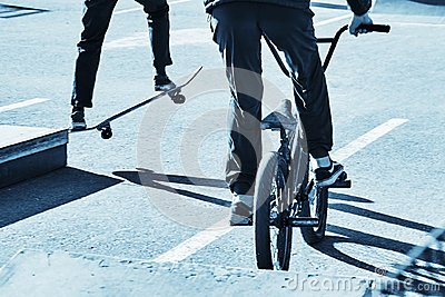 Skateboarder and bicycler. Blue toning