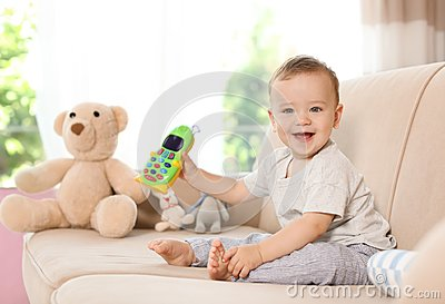 Adorable little baby with toy phone on sofa