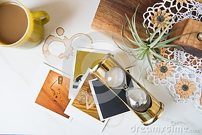 Retro 1970s Themed Still Life with Brass Hourglass Polaroids and Pyrex mug