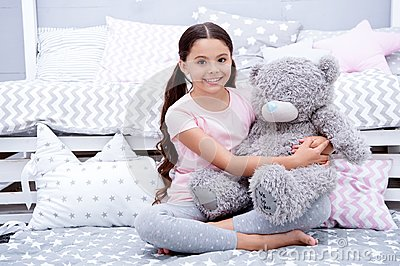 Favorite toy. Girl child sit on bed hug teddy bear in her bedroom. Kid prepare to go to bed. Pleasant time in cozy