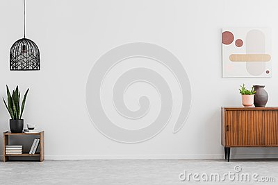Retro, wooden cabinet and a painting in an empty living room interior with white walls and copy space place for a sofa. Real photo