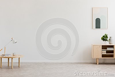 Desk lamp on a small table and a simple, wooden cabinet in an empty living room interior with white wall and place for a sofa. Rea