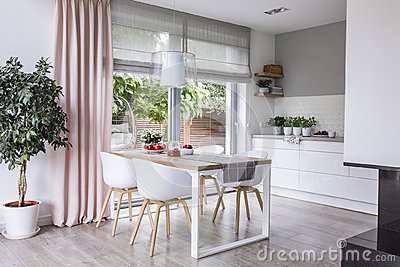 Gray roman shades and a pink curtain on big, glass windows in a