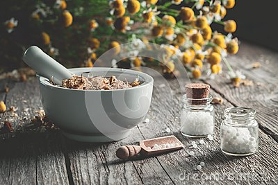 Mortar of dried healing herbs, homeopathic globules and bunch of chamomile plant.