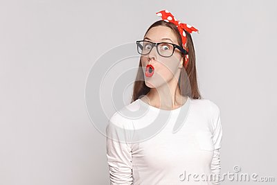 wow its unbelievable, portrait of beautiful emotional young woman in white t-shirt with freckles, black glasses, red lips and