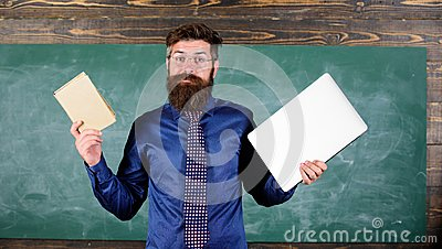 Teacher bearded hipster holds book and laptop. Choose right teaching method. Modern instead outdated. Teacher choosing