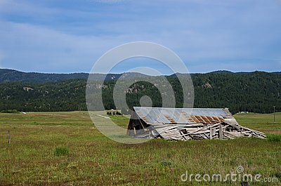 Old and Weathered Home Collapsed and Silent in the Forgotten Field