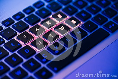 Fake news written on a backlit keyboard in a blue ambiant light