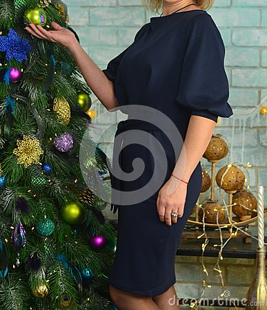Woman in a blue dress with a red thread on her arm, stands near the Christmas tree, holds a toy