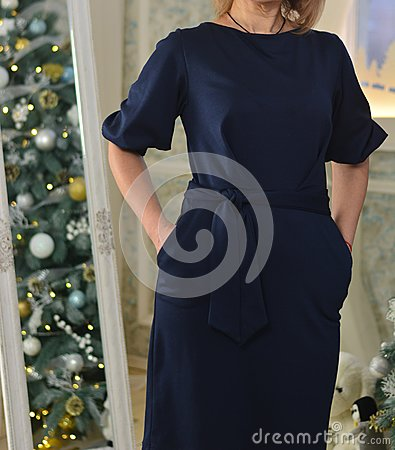 A woman in a blue dress is standing on the background of a mirror in which a Christmas tree is reflected. hands in pockets