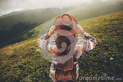 travel and wanderlust concept. stylish traveler hipster girl holding hat, with backpack and windy hair, walking in mountains in c